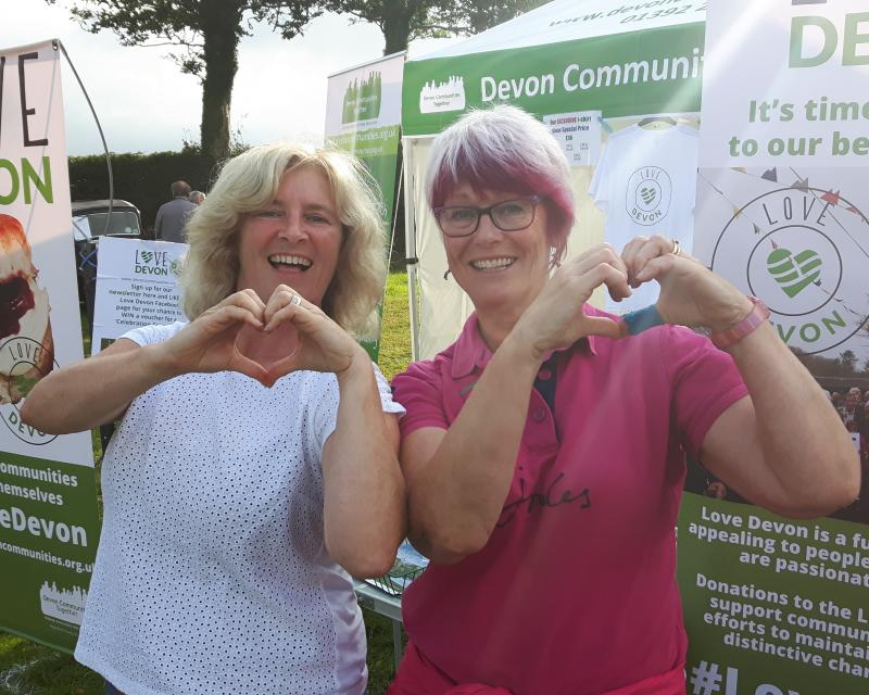 Two people making a heart shape each with both hands in front of Love Devon banners