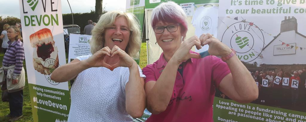 Two people making heart symbols with their hands beside a Love Devon stand