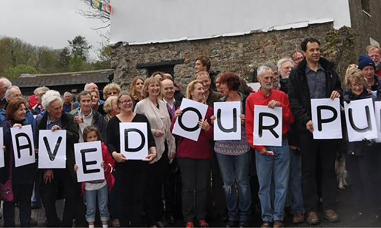 "People in a line holding letters which spell ""SAVED OUR PUB"""
